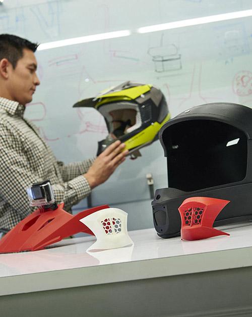 Pracownik biura projektowego trzyma kask wydrukowany w 3D