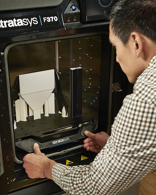 Pracownik biura projektowego wyjmuje gotowy druk z drukarki 3D